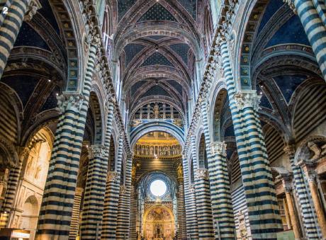 2 — Revêtue de marbres tantôt clairs tantôt sombres, élégamment pavée de scènes bibliques, la cathédrale de Sienne abrite un autre joyau, la bibliothèque Piccolomini, décorée de fresques peintes par Pinturicchio.