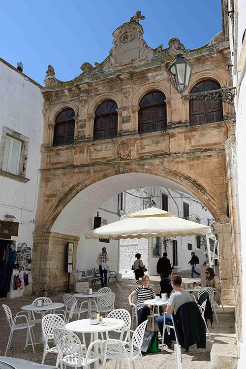 """L'Arco Scoppa. Cette loggia suspendue datant du XVIIIe siècle participe au charme lumineux de la """"città bianca"""", la ville blanche aux ruelles enlacées et pentues."""