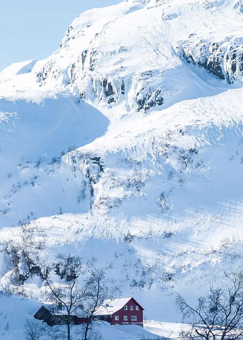 Parée de ses habits d'hiver, la nature perd un peu de sa rudesse pour faire l'éloge poétique de la solitude et de l'immensité. Le train Flamsbana parcourt  de sublimes paysages faits de cascades glacées et de montagnes duveteuses, ponctuées de maisons esseulées qu'on sait très chaleureuses dans leurs intérieurs.